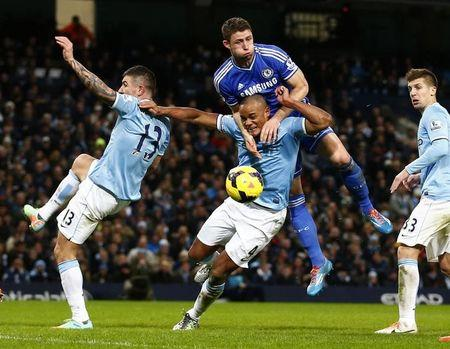 Chelsea's Cahill challenges Manchester City's Kompany during their English Premier League soccer match at the Etihad Stadium in Manchester
