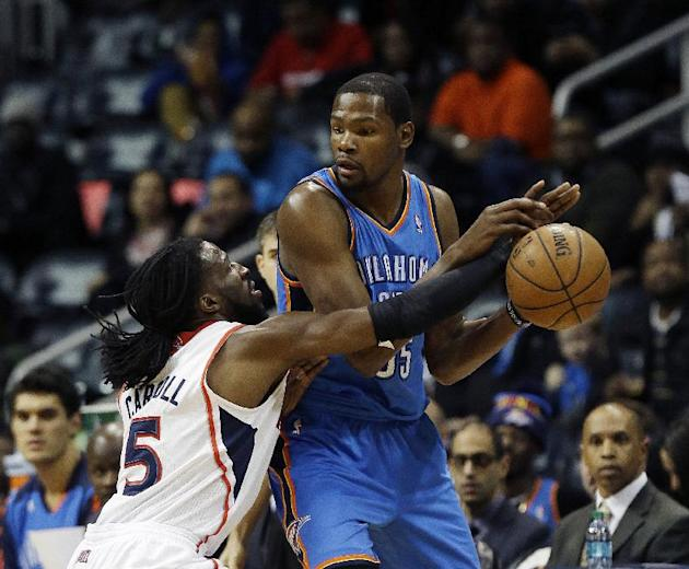 Atlanta Hawks forward DeMarre Carroll (5) reaches for the ball as he defends Oklahoma City Thunder forward Kevin Durant in the first half of an NBA basketball game Tuesday, Dec. 10, 2013, in Atlanta