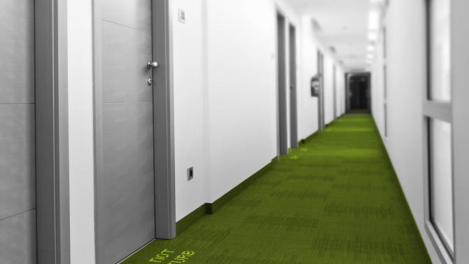 "In this computer-generated image made available by Royal Philips NV, Monday, Nov. 18, 2013, a LED sign with glowing lights reading ""Do Not Disturb"" drives the message home in a fictional hotel corridor. That option is on its way as two European companies, Philips and carpet-maker Desso have developed a system in which colored LEDs are combined with specialized carpets to make tailored hotel signs or directions to airport boarding gates that appear underfoot instead of on walls. (AP Photo/Philips)"