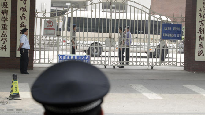 A van with tinted windows leaves under a tight security from the hospital where blind activist lawyer Chen Guangcheng was known to be recuperating in Beijing, Saturday, May 19, 2012. Chen Guangcheng told The Associated Press Saturday that he is now at the Beijing airport after leaving hospital.  (AP Photo/Ng Han Guan)