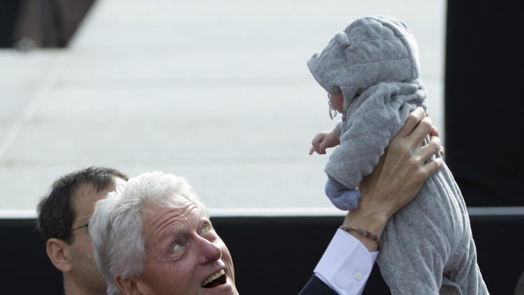 Former President Bill Clinton holds up a baby during a campaign event for President Barack Obama in the State Capitol Square, Sunday, Nov. 4, 2012, in Concord, N.H. (AP Photo/Carolyn Kaster)