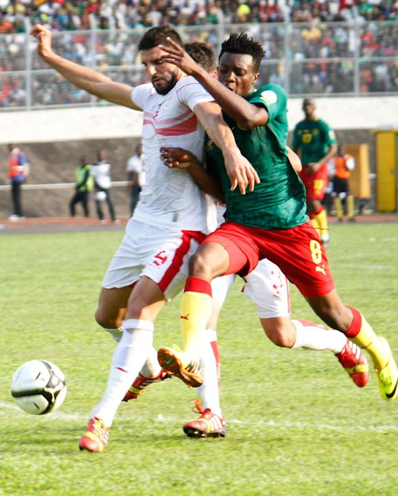 Cameroon's Benjamin Moukandjo, right, challenges Tunisia's Saber Khlifa in their World Cup qualifying playoff second leg soccer match, in Yaounde, Cameroon, Sunday, Nov. 17, 2013. Cameroon qualified f