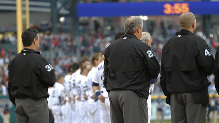 Umpires gather for a moment of silence for umpire Wally Bell before Game 3 of the American League baseball championship series between the Boston Red Sox and the Detroit Tigers, Tuesday, Oct. 15, 2013, in Detroit. Bell died Monday of a heart attack. (AP Photo/Paul Sancya)