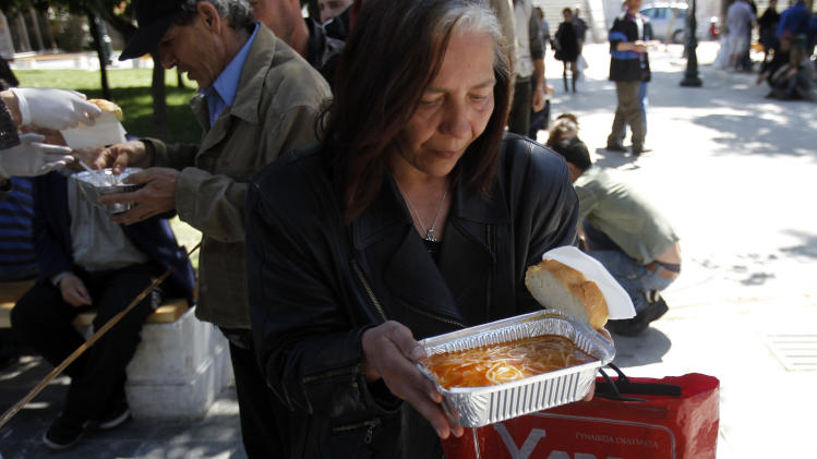A woman receives a free meal  during a soup kitchen organized by a Greek humanitarian group  in Athens'  main Syntagma square on Sunday, April 1 2012. Greece's  austerity cutbacks have deepened  the economic recession, and torn holes in the country's social fabric. Unemployment has hit a record high of 21 percent, and thousands of Greeks depend on church and municipal soup kitchens for sustenance. (AP Photo/Kostas Tsironis)