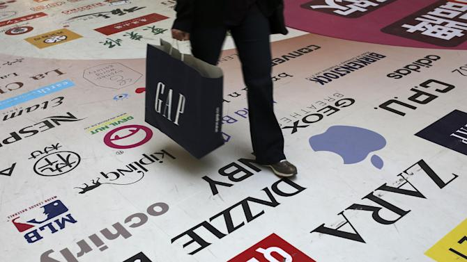 FILE - In this Oct. 21, 2014 file photo, a shopper walks across a floor displaying fashion brands and restaurants' names at a shopping mall in Beijing, China. This holiday season, some companies are hoping to make it as simple to shop on the other side of the world as it is to buy from a store down the block. (AP Photo/Andy Wong, File)