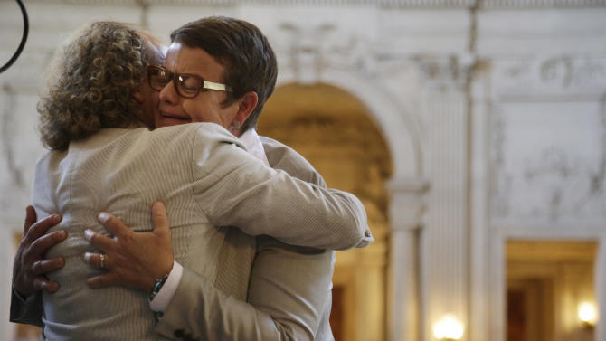 Kris Perry, right, is hugged by a supporter after marrying Sandy Stier in a ceremony presided by California Attorney General Kamala Harris at City Hall in San Francisco, Friday, June 28, 2013. Stier and Perry, the lead plaintiffs in the U.S. Supreme Court case that overturned California's same-sex marriage ban, tied the knot about an hour after a federal appeals court freed same-sex couples to obtain marriage licenses for the first time in 4 1/2 years. (AP Photo/Marcio Jose Sanchez)