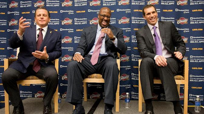 Cleveland Cavaliers owner Dan Gilbert, left, gestures as new head coach Mike Brown, center, and general manager Chris Grant laugh during an NBA basketball news conference, Wednesday, April 24, 2013, in Independence, Ohio. Brown, who led the Cavs to the NBA playoffs in each of his five seasons with the club, has reunited with a team and owner who fired him after Cleveland was eliminated from the 2010 playoffs. (AP Photo/Jason Miller)
