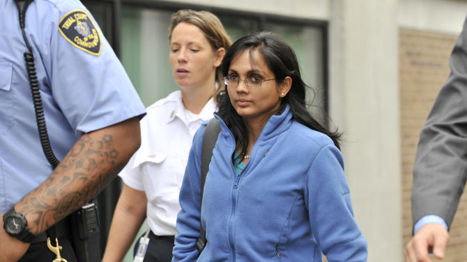 """FILE - In a Wednesday, Oct. 10, 2012 file photo, Annie Dookhan, center, is leaves a Boston courthouse escorted by court officers and her lawyer. Gov. Deval Patrick has ordered a """"file-by-file review"""" of every case handled by Dookhan, a Massachusetts chemist accused of faking test results at a now-closed government lab, as authorities continue to deal with the fallout from a scandal that threatens to unravel thousands of criminal cases. (AP Photo/Josh Reynolds, File)"""
