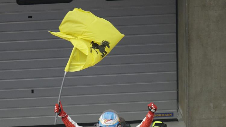 Ferrari driver Fernando Alonso of Spain stands on his car and waves a flag as he celebrates his win at the Chinese Formula One Grand Prix in Shanghai, China, Sunday, April 14, 2013. (AP Photo/Mark Baker)