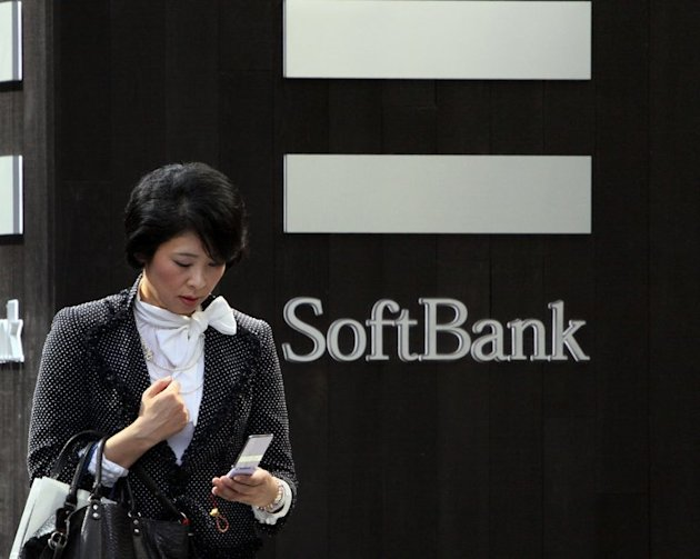 A pedestrian uses her mobile phone before a Softbank mobile phone shop in Tokyo on October 12, 2012