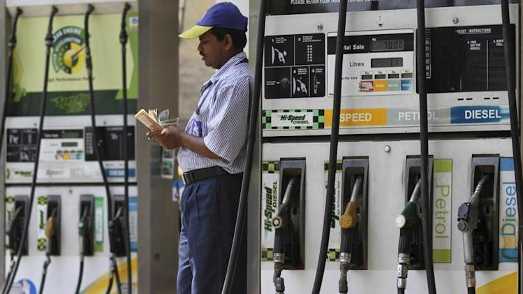 An employee counts money at a fuel station in Kolkata