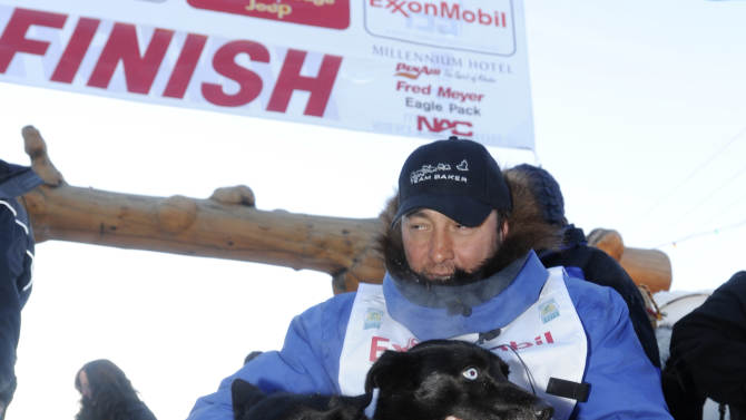 FILE - In this March 15, 2011 file photo, musher John Baker pets his lead dogs Snickers and Velvet after winning the the 2011 Iditarod Trail Sled Dog Race, in Nome, Alaska.  The 2012 race has its ceremonial start in Anchorage on Saturday, Mar. 3. A winter of heavy snow in Alaska is keeping trail breakers busy clearing the route of the 1,000-mile Iditarod Trail Sled Dog Race, but no one can remove other weather-related challenges like jumbled ice along the western coast and the heightened possibility of run-ins with grouchy moose.  (AP Photo/The Anchorage Daily News, Bob Hallinen, File)