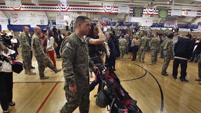 In this Nov. 30, 2012 photo, U.S. Army 1st Lt. Aaron Dunn walks with his wife Leanne, holding their baby Emma, after they they reunited at an arrival ceremony for soldiers returning from a deployment in Afghanistan, at Ft. Carson, in Colorado Springs, Colo. Dunn deployed to the Hindu Kush mountains close to the border with Pakistan, where his unit was charged with engaging Taliban fighters, and with mentoring Afghan Government soldiers who will soon be left to fight alone as U.S. combat forces steadily draw down after more than ten years. (AP Photo/Brennan Linsley)