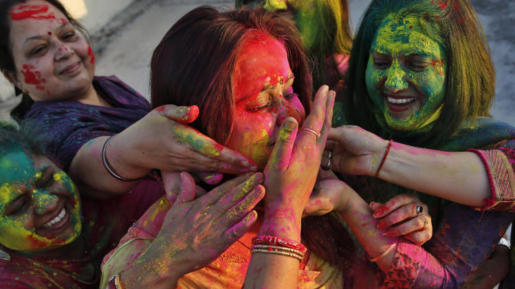 "Indian women smear colors on their faces as they celebrate ""Holi,"" a festival of colors, in Allahabad, India, Sunday, March 16, 2014. The festival heralds the arrival of spring. (AP Photo/ Rajesh Kumar Singh)"