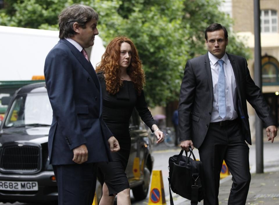 Former News International chief executive Rebekah Brooks, center, accompanied by her husband Charlie Brooks, left arrives to appear at Southwark Crown court on charges relating to the phone hacking scandal, in London, Friday, June 22, 2012. (AP Photo/Lefteris Pitarakis)