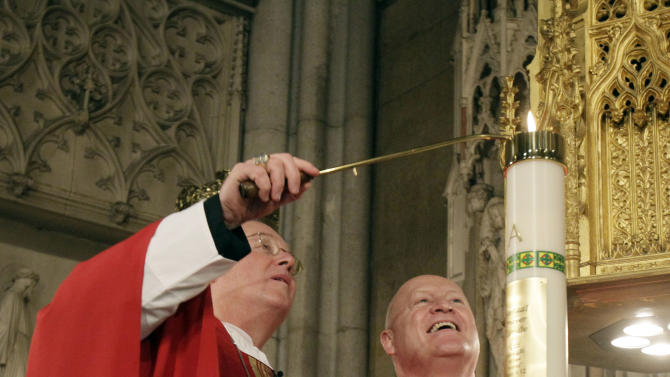 Archbishop Timothy M. Dolan, left, is joined by Msgr. Robert Ritchie, rector of St. Patrick's Cathedral, as he lights the physical, virtual candle in New York's St. Patrick's Cathedral, Thursday morning, June 30, 2011. The candle represents all virtual prayer candles lit through the cathedral's newly revamped website. (AP Photo/Richard Drew)