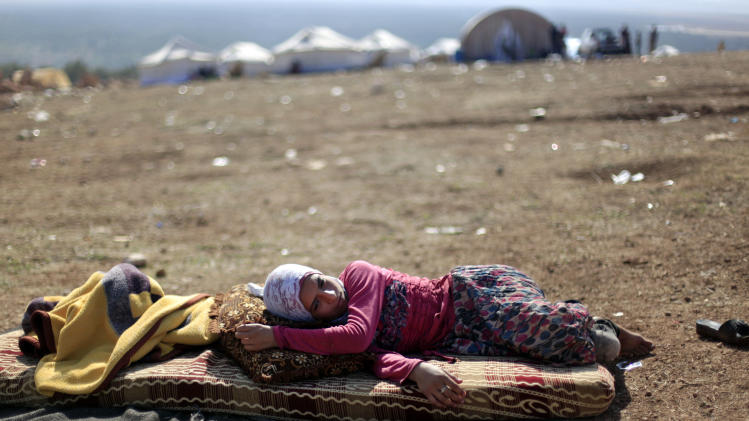 A Syrian girl who fled with her family from the violence in their village, rests at a displaced camp, in the Syrian village of Atma, near the Turkish border with Syria, Monday, Nov. 5, 2012. (AP Photo/ Khalil Hamra)