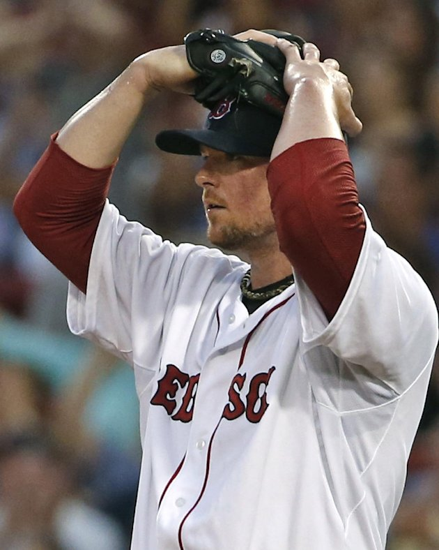 Boston Red Sox starting pitcher Jon Lester reacts as center fielder Brock Holt makes a difficult catch of a fly out by Minnesota Twins' Brian Dozier w...