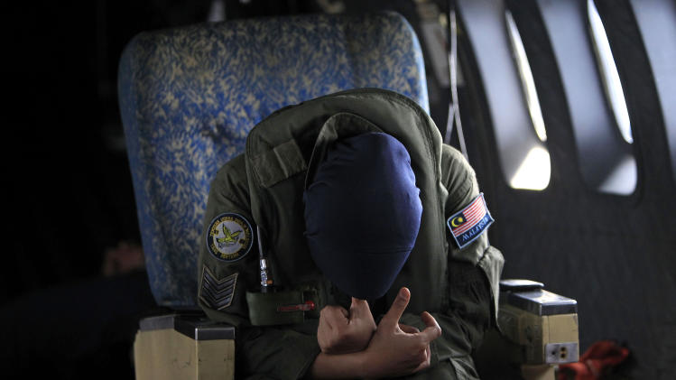 A crew member of a Royal Malaysian Air Force CN-235 aircraft rests after long hours working in a search and rescue operation for the missing Malaysia Airlines plane over the Straits of Malacca, Thursday, March 13, 2014. Planes sent Thursday to check the spot where Chinese satellite images showed possible debris from the missing Malaysian jetliner found nothing, Malaysia's civil aviation chief said, deflating the latest lead in the six-day hunt. The hunt for the missing Malaysia Airlines flight 370 has been punctuated by false leads since it disappeared with 239 people aboard about an hour after leaving Kuala Lumpur for Beijing early Saturday. (AP Photo/Lai Seng Sin)