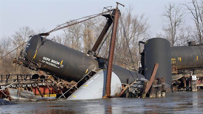 A containment boom floats in Mantua Creek Saturday, Dec. 1, 2012, near freight train tank cars that derailed Friday in Paulsboro, N.J. Residents in an area of about 12 blocks near the derailment remain out of their homes as officials continued their efforts to clear a hazardous gas that spewed from a ruptured freight train car. The precautionary evacuations were ordered late Friday, hours after a train derailment, and will likely remain in effect throughout the weekend and possibly longer. The order came after readings showed higher levels of vinyl chloride in the air.  (AP Photo/Mel Evans)
