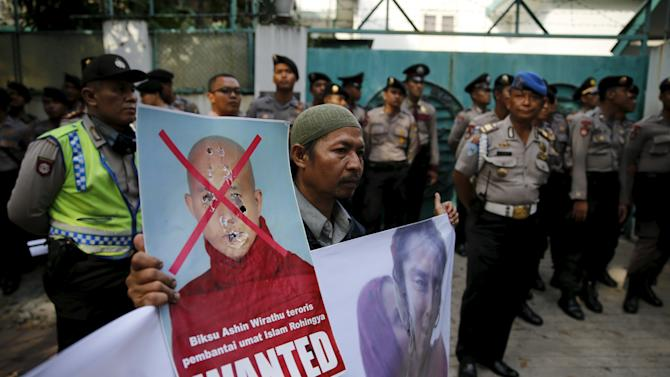 An Indonesian hardline Islamic Defenders Front member holds a poster of Buddhist monk Ashin Wirathu during a protest in front of the Myanmar Embassy in Jakarta