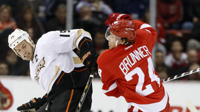 Anaheim Ducks center Ryan Getzlaf (15) is knocked off the puck by Detroit Red Wings center Damien Brunner (24) in the first period of an NHL hockey game on Friday, Feb. 15, 2013, in Detroit. (AP Photo/Duane Burleson)