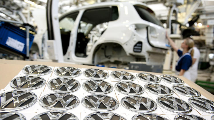 """FILE - In this March 7, 2012 file picture employees work at an assembly line of the Volkswagen factory in Wolfsburg, Germany. German automaker Volkswagen AG says Wednesday, Oct. 24, 2012, net profit rose 58 percent in the third quarter because of an accounting boost from its takeover of Porsche. The company's operating profits fell however. Volkswagen said it was sticking to its earnings forecast despite what it called """"growing headwinds"""" in the business environment. Net profit rose to euro 11.38 billion (US dollar 14.80 billion) from euro 7.14 billion in the same quarter last year. Sales rose 27 percent to euro 48.84 billion. (AP Photo/dapd, Nigel Treblin, File)"""