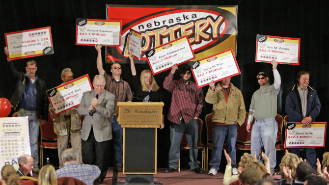 FILE - In this Feb. 22, 2006 file photo, the eight ConAgra plant workers hold up their ceremonial checks after winning the $365 million dollar Nebraska Powerball lottery at a news conference in Lincoln, Neb. Work pools for big jackpots are often fraught with controversy, resulting in lawsuits, broken friendships and worse: delayed payouts. (AP Photo/Nati Harnik/File)