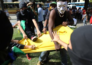 Masked anti-World Cup protesters rip apart a Brazilian national team soccer jersey on Thursday. (AP)