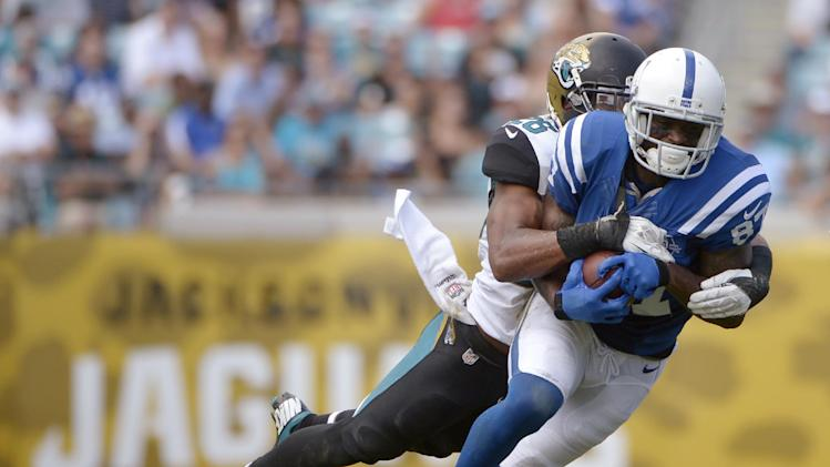 In this Sept. 29, 2013, photo, Indianapolis Colts wide receiver Reggie Wayne (87) catches a pass in front of Jacksonville Jaguars free safety Josh Evans during an NFL football game in Jacksonville, Fla.  Wayne is trying to return from a torn anterior cruciate ligament in his right knee