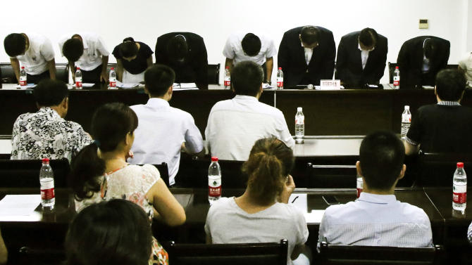 In this photo taken Wednesday, July 17, 2013, representatives from Asiana Airlines bow to express their apologies for the airliner crash in San Francisco during a meeting with relatives of passengers and lawyers at a conference room at Jiangshan High School in Jiangshan city in eastern China's Zhejiang province. (AP Photo) CHINA OUT