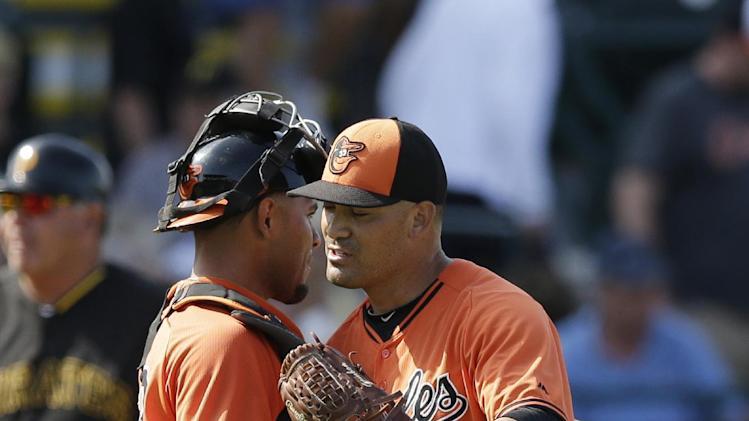 Baltimore Orioles catcher Johnny Monell, left, hugs pitcher Eddie Gamboa after their 7-6 win over the Pittsburgh Pirates in a spring exhibition baseball game in Bradenton, Fla., Monday, March 10, 2014