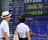 An elderly couple gaze at a share prices board in the window of a securities company in Tokyo on September 26. Asian markets were mostly lower on Monday as better-than-expected US growth data failed to offset concerns over corporate earnings