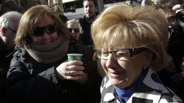 "A woman, who won part of the first prize of ""El Gordo"", cries outside a lottery shop where the winning lottery number was sold in Leganes"