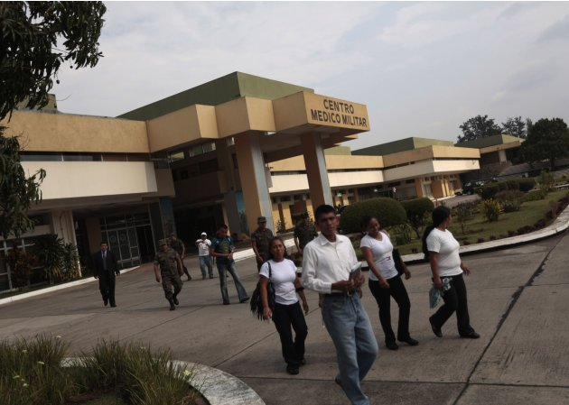 Soldiers and civilians walk outside Centro Medico Militar where former Guatemalan dictator Rios Montt has been undergoing medical treatment in Guatemala City