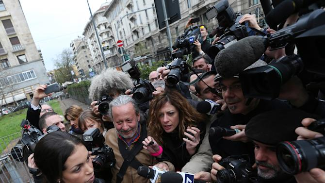 Karima el-Mahroug, also known as Ruby, bottom left, a Moroccan woman at the center of ex-Premier Silvio Berlusconi's sex-for-hire trial, reads a statement to reporters outside Milan's court house, Italy, Thursday, April 4, 2013. The Moroccan woman at the center of ex-Premier Silvio Berlusconi's sex-for-hire trial has denounced what she says is psychological warfare being waged against her by Italian prosecutors. Ruby, read out a lengthy statement Thursday to a gaggle of reporters in front of Milan's courthouse denying she was a prostitute and insisting that prosecutors hear her side of the story. (AP Photo/Luca Bruno)