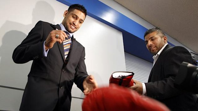 Amir Khan (L) tosses a glove into a box after autographing it while his manager Asif Vali (R) hands him another glove to sign before a media conference (Reuters)