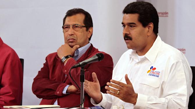 In this photo released by Miraflores Presidential Press Office, Venezuela's Vice President Nicolas Maduro, right, addresses the nation from Miraflores presidential palace as Governor Adan Chavez, the older brother of President Hugo Chavez, looks on in Caracas, Venezuela, Tuesday, March 5, 2013. Maduro met with top Venezuelan government ministers, the military high command and all 20 loyalist governors in Caracas following word of President Hugo Chavez's deteriorating health. (AP Photo/Miraflores Presidential Press Office)