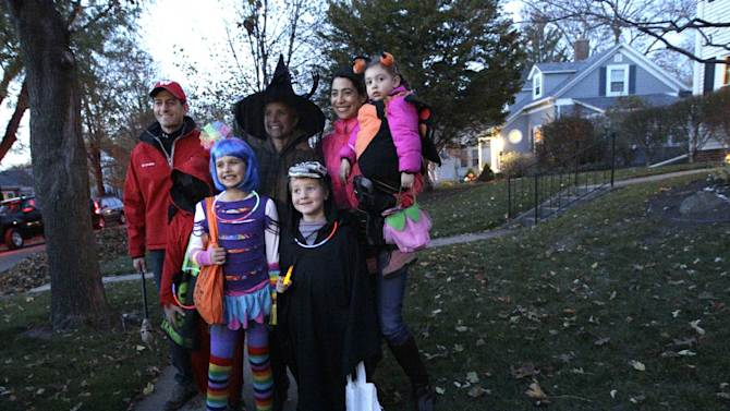 Republican vice presidential candidate, Rep. Paul Ryan, R-Wis., poses for a photo with his family, from left, Charlie dressed up as the Unknown Phantom, Liza as Katy Perry, Janna, as a witch, Sam as the Grim Reaper, his sister-in-law Zoe Ryan and her daughter Zaydee May while out trick or treating, Wednesday, Oct. 31, 2012, in Janesville, Wis.  (AP Photo/Mary Altaffer)