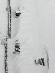 Stranded vehicles are buried under snow along a road in Nakashibetsu, Hokkaido, northern Japan, Sunday, March 3, 2013. At least eight people were killed after their vehicles got trapped in heavy snow in Hokkaido over the weekend, local reports said. (AP Photo/Kyodo News) JAPAN OUT, MANDATORY CREDIT, NO LICENSING IN CHINA, HONG KONG, JAPAN, SOUTH KOREA AND FRANCE