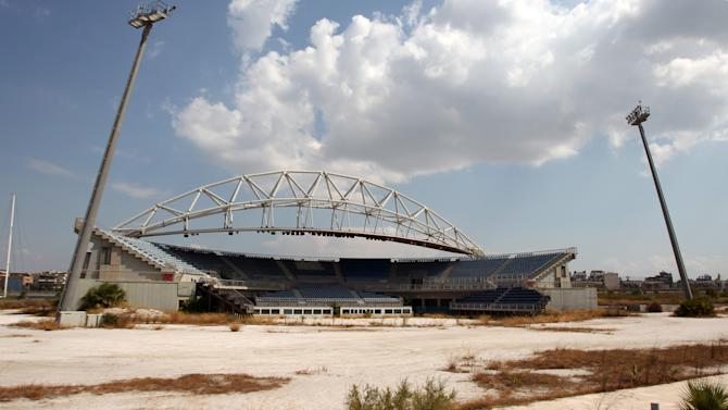 The Olympic beach volleyball lies abandoned in southern Athens, Thursday, Aug. 2, 2012. The purpose-built stadium has seen minimal use _ mostly for concerts _ since the Athens 2004 Olympics. Eight years after the Athens Games, many of the venues remain abandoned or rarely used, focusing public anger on past governments as the country struggles through a fifth year of recession and a debt crisis that has seen a surge in poverty and unemployment.  (AP Photo/Thanassis Stavrakis)