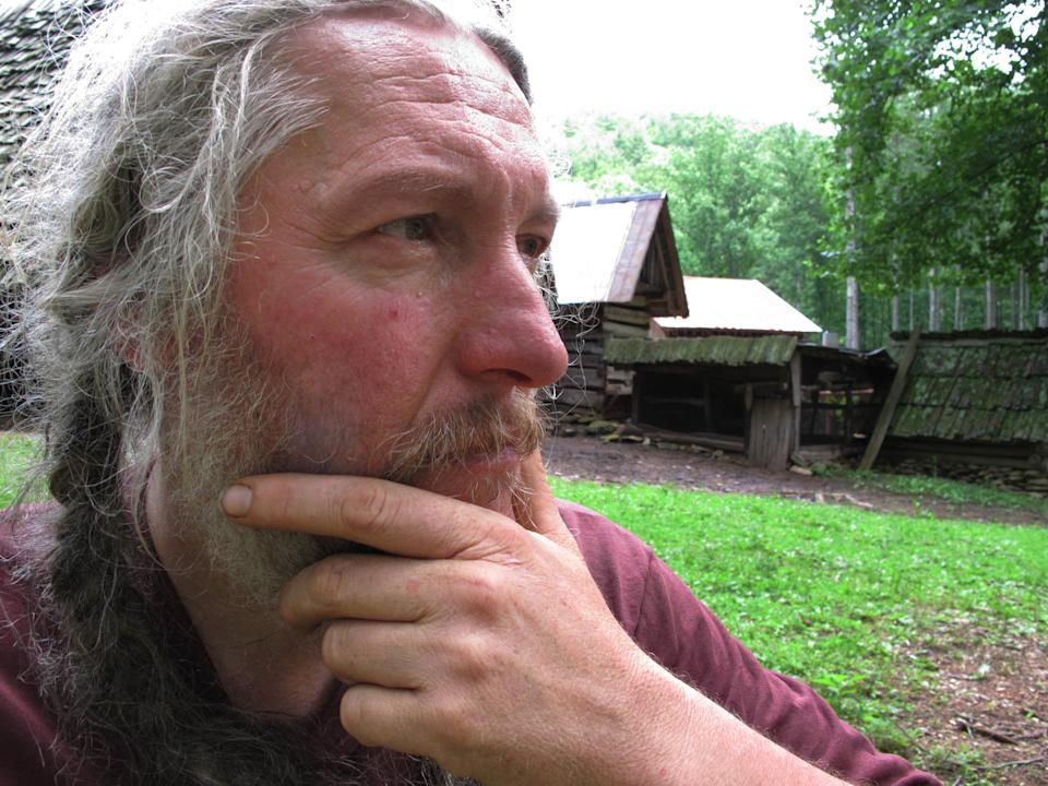 Eustace Conway sits in front of the horse barn at his Turtle Island Preserve in Triplett, N.C., on Thursday, June 27, 2013. People come from all over the world to learn natural living and how to go off-grid, but local officials ordered the place closed over health and safety concerns. (AP Photo/Allen Breed)