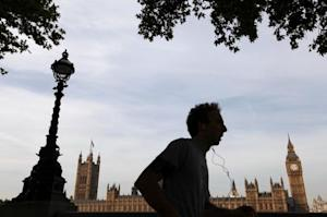 A jogger runs along the south bank in front of the Houses of Parliament on a sunny autumn day in London