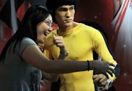 A tourist strikes a pose next to a wax figure of legendary Kung Fu master Bruce Lee, in Hong Kong, on October 25, 2011. Hailed as cinema's first martial arts hero and a cinematic bridge between the cultures of East and West, Lee helped put Hong Kong on the movie world map