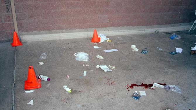 In this image released by the Pima County Sheriff's department, medical supplies, markers, other debris and what appears to be blood, are seen in the aftermath of the Tucson shooting rampage that killed six people and wounded former U.S. Rep. Gabrielle Giffords and 12 others in January 2011.  Authorities released more than 300 photos on Tuesday, May 21, 2013, made by investigators during their investigation in the parking lot of the shopping center where the shooting took place.  (AP Photo/Pima County Sheriff)