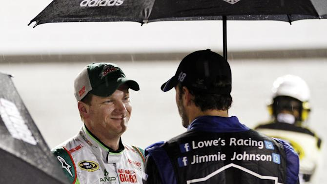 Dale Earnhardt Jr., left, talks with Jimmie Johnson, right, during a rain delay for the NASCAR Sprint Cup Series auto race at Richmond International Raceway in Richmond, Va., Saturday, Sept. 8, 2012. (AP Photo/Steve Helber)