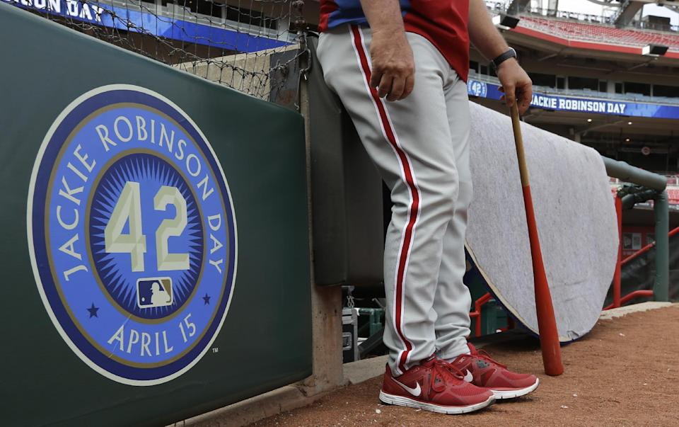 A Philadelphia Phillies coach stands next to a sign honoring Jackie Robinson day prior to a baseball game against the Cincinnati Reds, Monday, April 15, 2013, in Cincinnati. (AP Photo/Al Behrman)