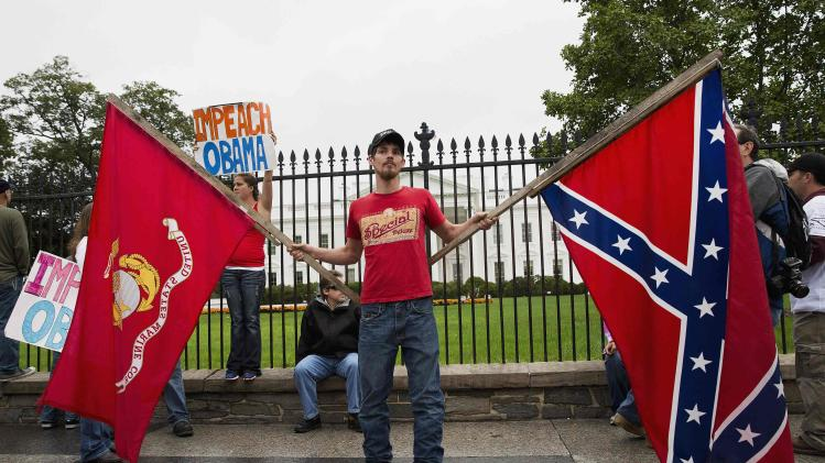 """A protester with """"Million Vet March on the Memorials"""", stands in front of White House holding the Marine Corps flag and Confederate flag in Washington"""