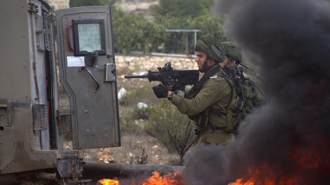 Israeli troops take aim during clashes with Palestinians, near Ramallah, West Bank, Friday, Oct. 9, 2015. Recent days have seen a string of attacks by young Palestinians with no known links to armed groups who have targeted Israeli soldiers and civilians at random, complicating Israeli efforts to contain the violence, which has been linked to tensions over a sensitive Jerusalem holy site. (AP Photo/Majdi Mohammed)