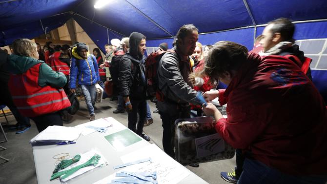 """Coloured bracelets are placed on the wrist of migrants on the second day of their evacuation and transfer to reception centers in France, during the dismantlement of the camp called the """"Jungle"""" in Calais"""